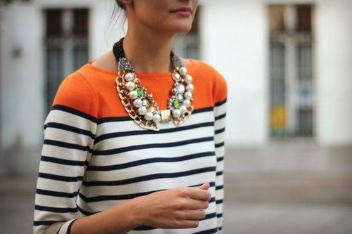 The pop of orange is great is this look as well as the mix of jewels, pearl and chain in the necklace